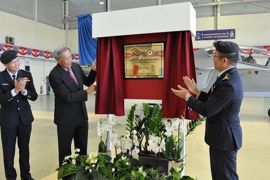 Dr Ng, accompanied by Major-General Hoo (right) and Commander Air Force Training Command, Colonel Benedict Ang, unveiling the plaque at the inauguration ceremony of the RSAF's new Advanced Jet Trainer, the Alenia Aermacchi M-346 aircraft. -- PHOTO: