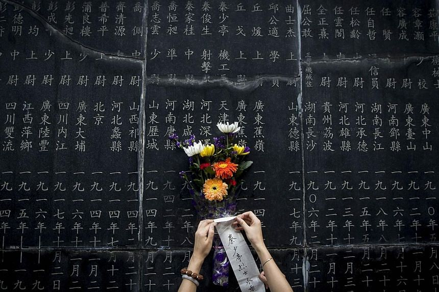 A mourner places a bunch of flowers onto a monument showing the names of people who died in battles against Japan during World War II at the Aviation Martyr Memorial to commemorate the 69th anniversary of victory over Japan in World War II in Nanjing