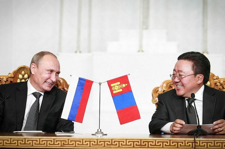 Russian President Vladimir Putin (left) smiles with Mongolian President Tsakhia Elbegdorj during a meeting in the Mongolian capital Ulan Bator on Sept 3, 2014. Russia's President Vladimir Putin on Wednesday unveiled a seven-point plan for peace