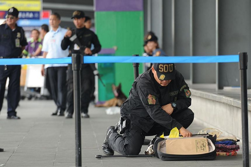 """A Philippine police bomb disposal unit member inspects abondoned luggage at the departure area of the airport's terminal three in Manila on Sept 1, 2014, hours after a utility vehicle containing an """"improvised explosive device"""" was found at the car p"""