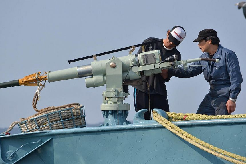 This file picture taken on April 26, 2014, shows crew members of a whaling ship checking a whaling gun or harpoon before departure at Ayukawa port in Ishinomaki City, northern Japan.Japan plans to resume its slaughter of minke whales in the Ant