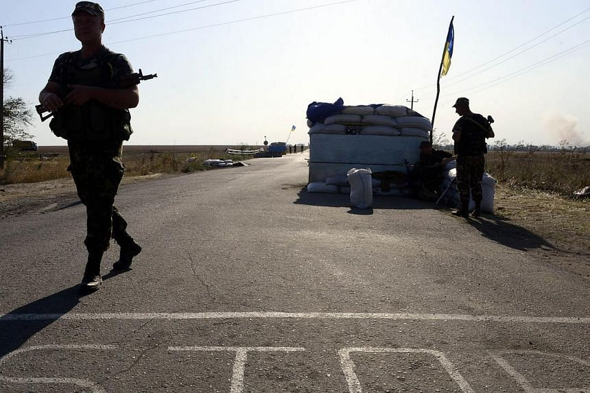 "Ukrainian fighters from the Azov Battalion stand guard at a checkpoint on the outskirts of Mariupol on Sept 2, 2014. Russian President Vladimir Putin and his Ukrainian counterpart Petro Poroshenko have agreed to a ""permanent ceasefire"" in fighti"