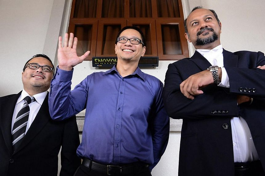 University of Malaya law lecturer Azmi Sharon (centre) waves to journalists as his lawyer Gobind Singh (right) looks on at the Sessions Court on Sept 2, 2014, after he was charged with sedition in Kuala Lumpur. -- PHOTO: AFP