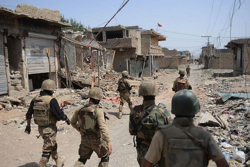 Pakistani soldiers patrol beside destroyed houses during a military operation against Taleban militants in the main town of Miranshah in North Waziristan on July 9, 2014.Pakistan's military said on Wednesday, Sept 3, 2014, it had killed more th