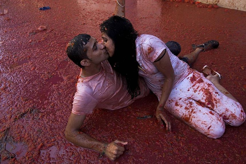 """A couple kisses during the annual """"tomatina"""" festivities in the village of Bunol, near Valencia on Aug 28, 2013.Two thousand tomato-wielding protesters are to stage a massive food fight in Amsterdam to protest Russia's ban on the import of Dutc"""