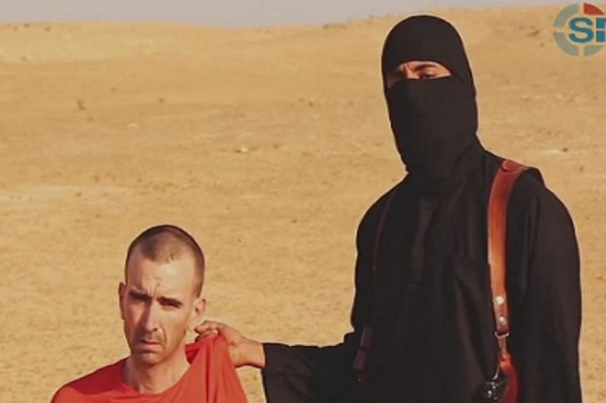 A still from a video purportedly showing threats being made to a man named as David Haines by a masked Islamic State (ISIS) fighter in an unknown location. The video was released by ISIS on Sept 2, 2014. -- PHOTO: REUTERS