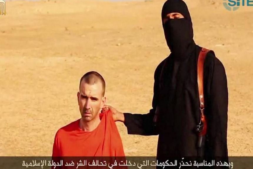 An image grab taken from a video released by the Islamic State (ISIS) and identified by private terrorism monitor SITE Intelligence Group on Sept 2, 2014, purportedly shows footage of a masked militant threatening to kill Briton David Cawthorne Haine