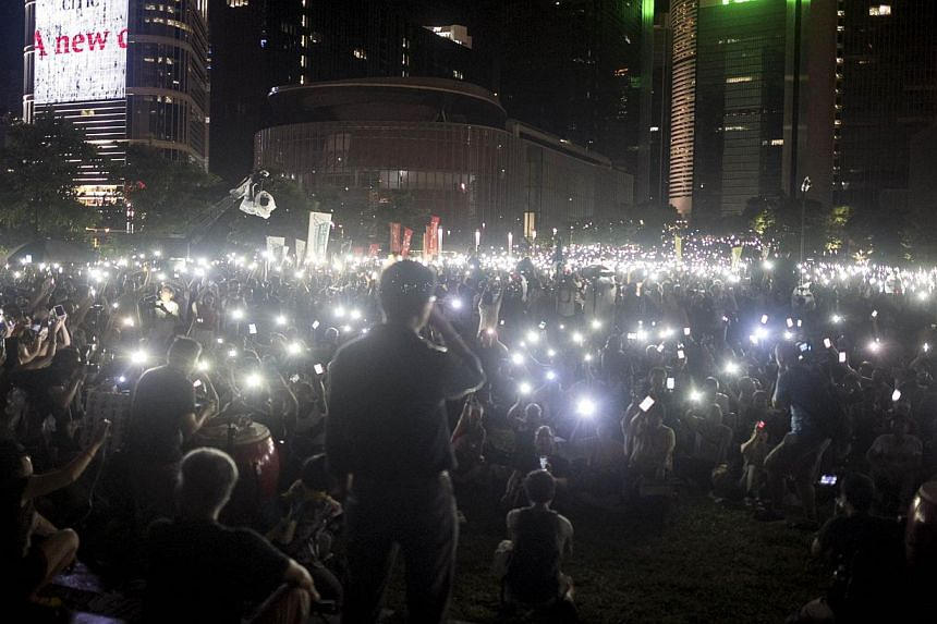Protesters wave their mobile phones and other electronic devices as they take part in a pro-democracy rally next to the Hong Kong government complex on Aug 31, 2014.China stressed on Wednesday that it would tolerate no foreign interference in H