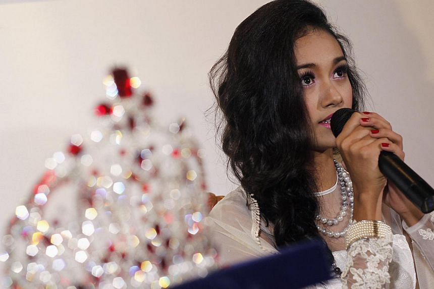 Dethroned beauty queen May Myat Noe gives a news conference, seated next to the 2014 Miss Asia Pacific World crown, at a restaurant in Yangon on Sept 2, 2014. -- PHOTO: REUTERS