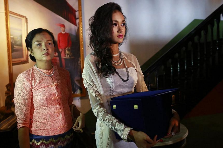 Dethroned beauty queen May Myat Noe (right), holding the box containing the 2014 Miss Asia Pacific World crown, stands next to her mother before giving a news conference at a restaurant in Yangon on Sept 2, 2014. -- PHOTO: REUTERS