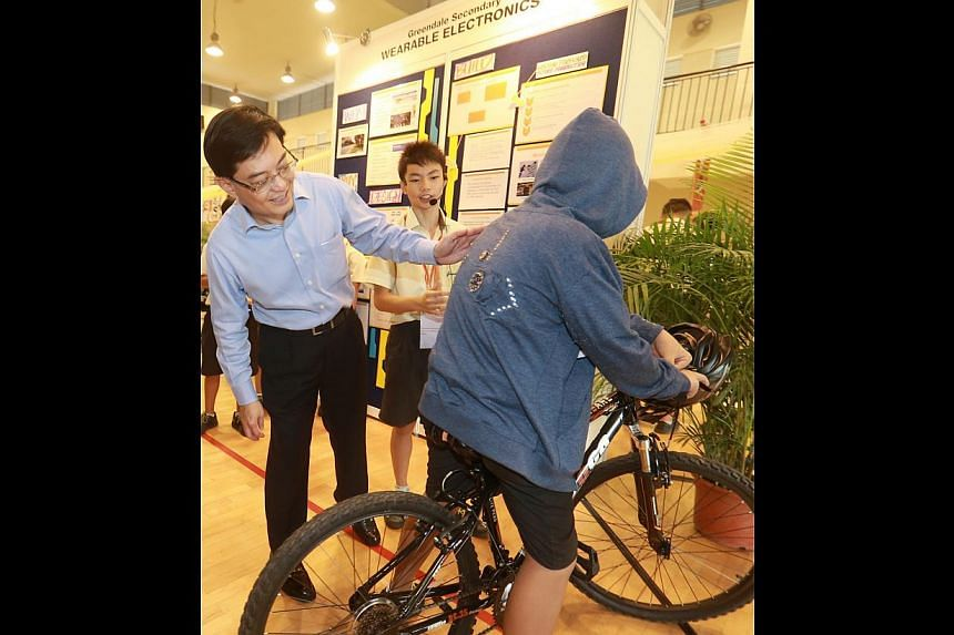 "Education Minister Heng Swee Keat checking out the ""cycling safety jacket"" donned by Greendale Secondary School student Lim Xuan Yi, as his group mate Norman Chin, 13, looks on."