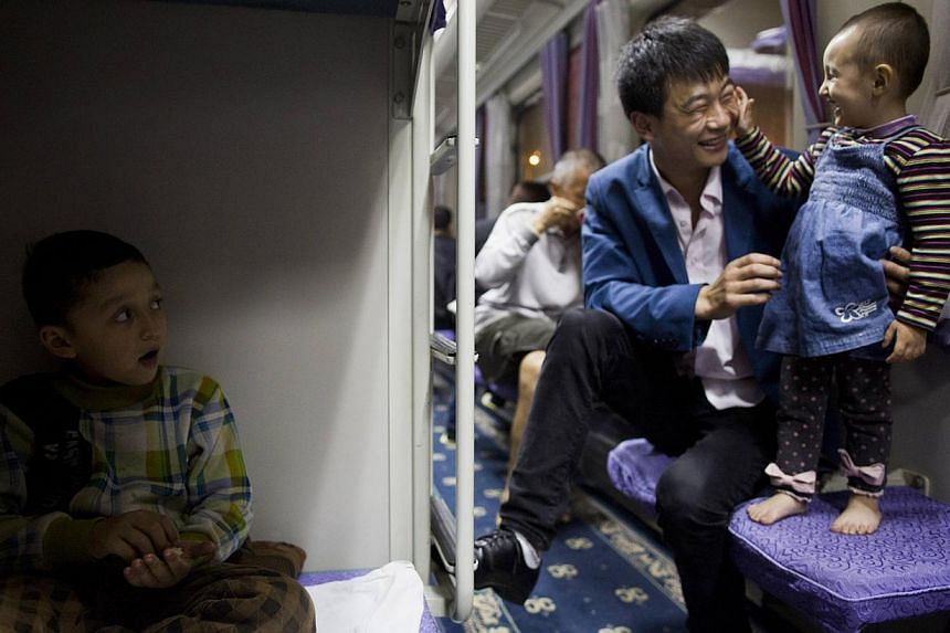 Uighur children play with a Han man on a train from Shanghai to Xingjiang, on May 14, 2014. The authorities are offering rewards of 10,000 yuan (S$2,000) a year to promote intermarriage in restive Xinjiang between ethnic minorities and China's d
