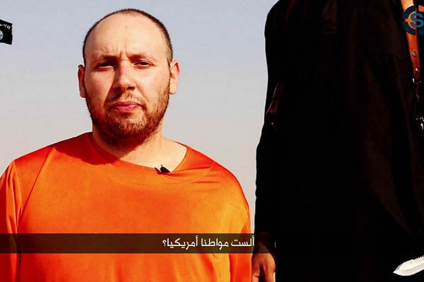 A video purportedly showing US journalist Steven Sotloff kneeling next to a masked Islamic State fighter holding a knife in an unknown location in this still image from a video released by the Islamic State on Sept 2, 2014. The video of the exec