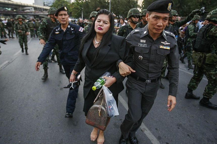 A policeman and soldiers leading a woman who showed her support for the army to safety and away from protesters against military rule at the Victory Monument in Bangkok, in this May 26, 2014 file photo.Since seizing power from the elected gover