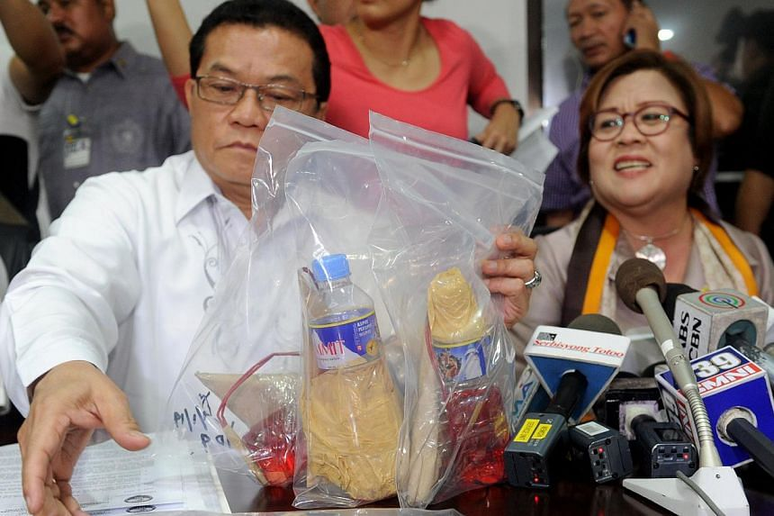 Justice Secretary Leila de Lima (right) and National Bureau of Investigation director Virgilio Mendez (left) display seized improvised firebombs and firearms in Manila on Sept 2, 2014 after three men, who were detained the day before at the airport w