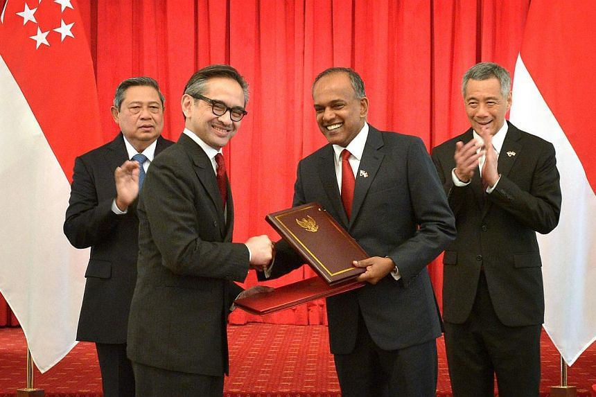Indonesian President Susilo Bambang Yudhoyono (left) and Singapore Prime Minister Lee Hsien Loong (right) look on as Indonesian Foreign Minister Marty Natalegawa (second from left) exchanges the treaty with Singapore Foreign Minister K. Shanmugam (se