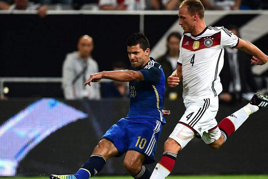 Argentina's striker Sergio Aguero (left) vies with Germany's defender Benedikt Howedes during a friendly football match between Germany vs Argentina in Duesseldorf, Germany, on Sept 3, 2014. -- PHOTO: AFP