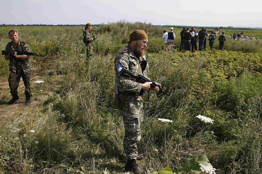 Armed pro-Russian separatists stand guard as monitors from the Organization for Security and Cooperation in Europe (OSCE) and members of a Malaysian air crash investigation team inspect the crash site of Malaysia Airlines Flight MH17, near the villag