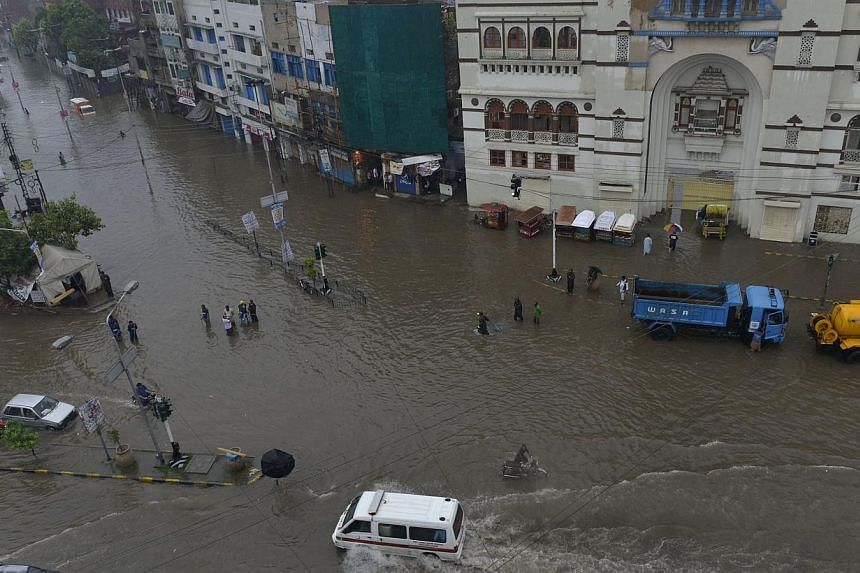 Pakistani residents and vehicles are pictured in a flooded street following heavy rain in Lahore on Sept 4, 2014.At least 25 people have been killed in roof collapses caused by heavy monsoon rains in Pakistan, officials said Thursday, as author
