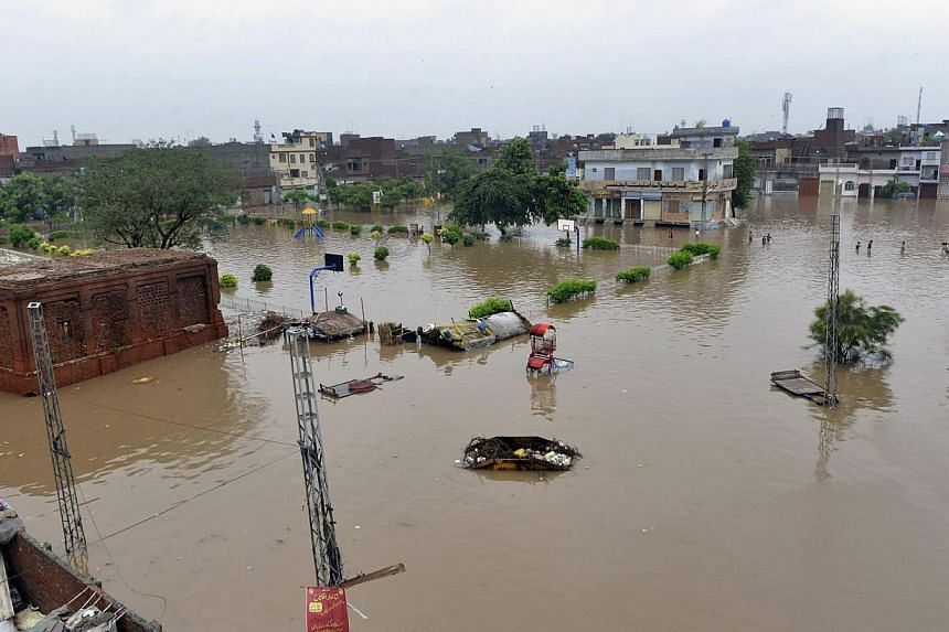 Pakistani residents wade through floodwaters following heavy rain in Lahore on Sept 4, 2014.At least 25 people have been killed in roof collapses caused by heavy monsoon rains in Pakistan, officials said Thursday, as authorities warned more int