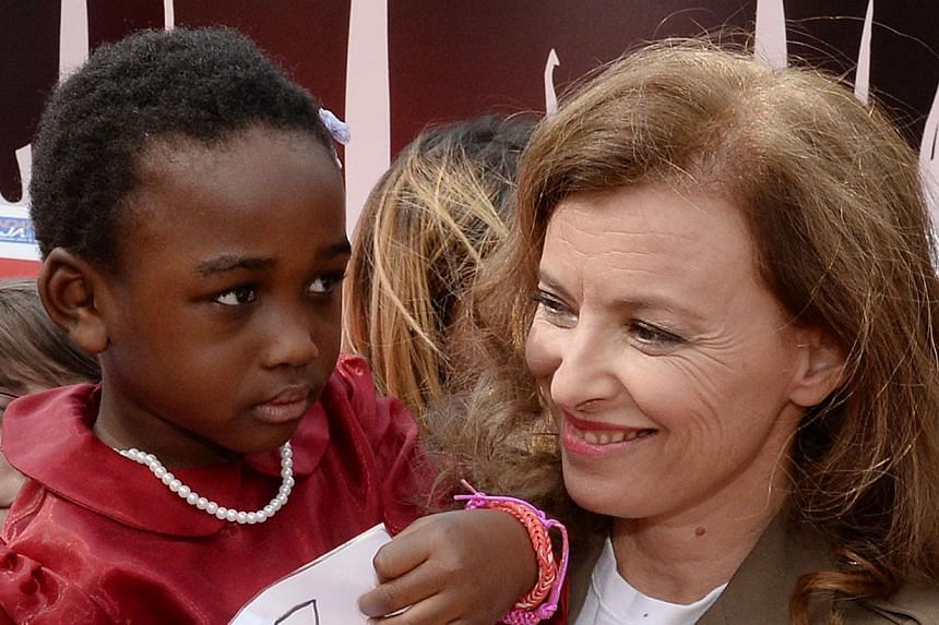 """Former French first lady Valerie Trierweiler poses with a young child holding a placard reading in French """"#Bring Back Our Sisters"""" during the inauguration of the temporary exhibition Bring Back Our Girls as part of the worldwide Bring Back Our Girls"""