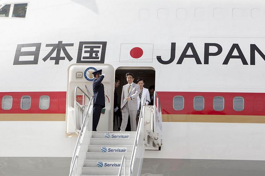 Japanese Prime Minister Shinzo Abe prepares to get off his plane upon his arrival in Port of Spain, Trinidad and Tobago on July 27, 2014. It emerged that details about the flight path and exact location of Mr Abe's plane had been posted on the Intern