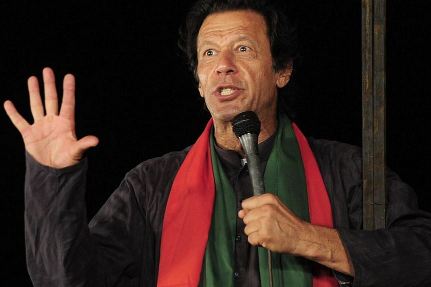 Pakistani cricketer-turned politician Imran Khan talks to supporters during an anti-government protest near the prime minister's residence in Islamabad on Sept 3, 2014. -- PHOTO: AFP