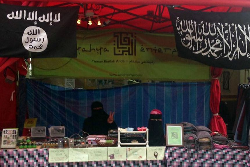 The Singapore company is seen here selling the flags (left), which are similar to the real one carried by an ISIS fighter in Syria (right).