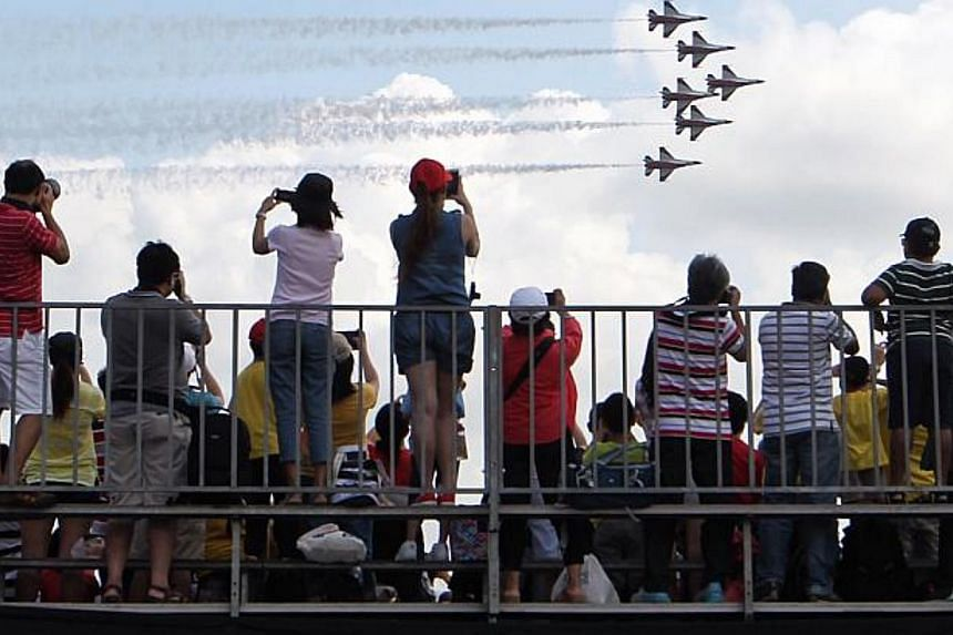 Visitors watching the morning aerial display by the Republic of Singapore Air Force's (RSAF) Black Knights, in a six-plane formation at the Singapore Airshow 2014 held at the Changi Exhibition Centre on Feb 16, 2014. -- PHOTO: ST FILE