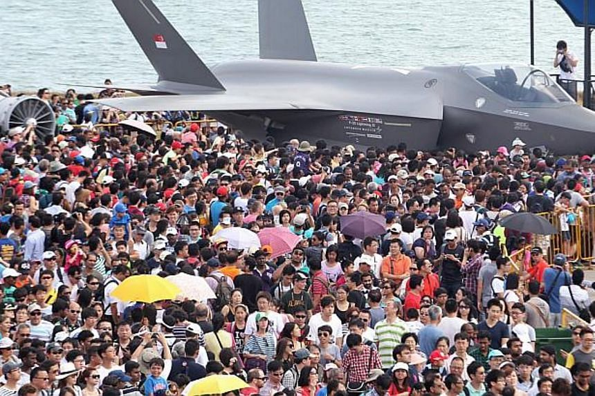 A mock-up of the Lockheed Martin F-35 Lightning II stealth fighter plane, surrounded by crowds at the Singapore Airshow 2014. -- PHOTO: ST FILE