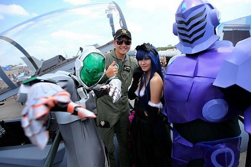 Cosplayers (from left) Roland Lee, Caitlin Sison and Kogin Ko, who were dressed as characters from Japanese anime Accel World, posing for photos with fighter pilot Captain Yeo Ze Ming of the Republic of Singapore Air Force, at the Singapore Airshow 2