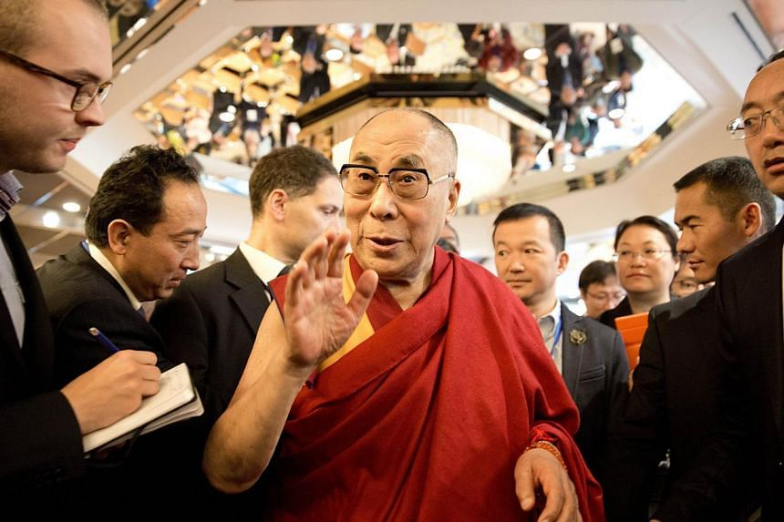 Tibetan spiritual leader Dalai Lama (middle) talks with journalists as he attends a Sino-Tibetan conference in Hamburg, northern Germany on Aug 27, 2014.-- PHOTO: AFP