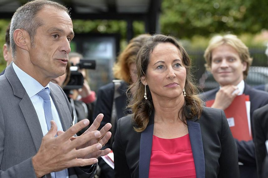 French minister for Ecology, Sustainable Development and Energy, Segolene Royal (middle) listens to chairman and CEO of Schneider Electric Jean-Pascal Tricoire (left) during a visit focusing on the energy transition on Sept 4, 2014 at the headquarter