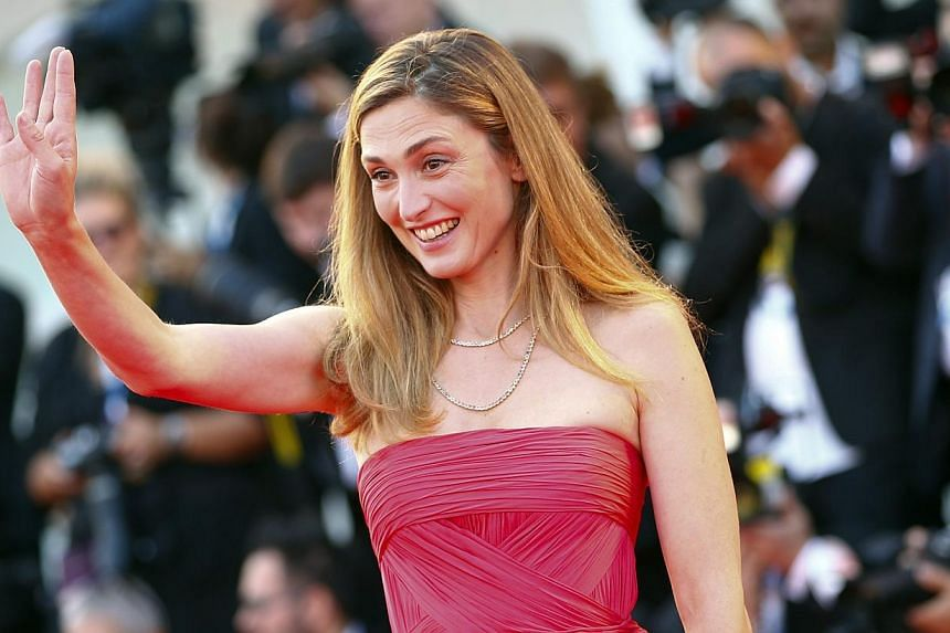 Actress Julie Gayet gestures as she arrives on the red carpet for the opening ceremony of the 71st Venice Film Festival in Venice Aug 27, 2014. -- PHOTO: REUTERS