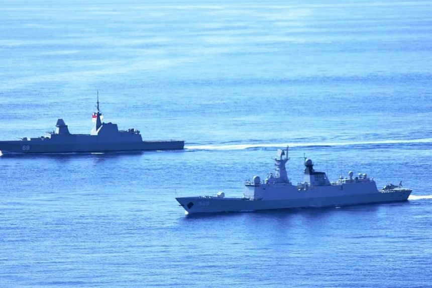 RSS Intrepid (background) participating in a bilateral naval exercise with Yulin. -- PHOTO: MINDEF