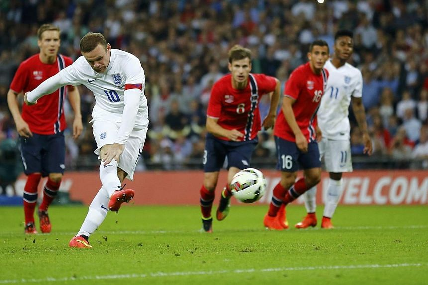 England captain Wayne Rooney shoots and scores his penalty during their international friendly match against Norway at Wembley Stadium in London on Sept 3, 2014. -- PHOTO: REUTERS
