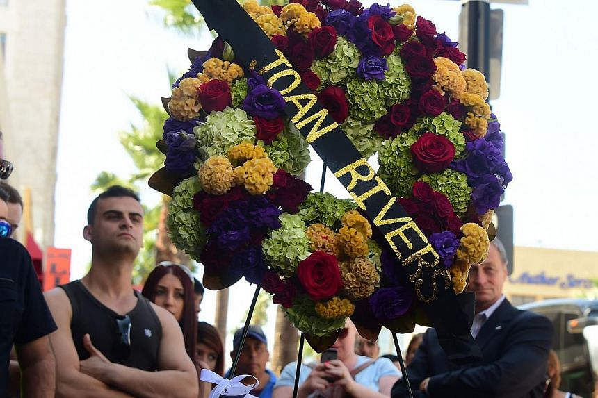 Onlookers gather beside a wreath of flowers placed on the Hollywood Walk of Fame Star for Joan Rivers in Hollywood, California on Sept 4, 2014, following news of the comedian's death in New York at the age of 81. -- PHOTO: AFP