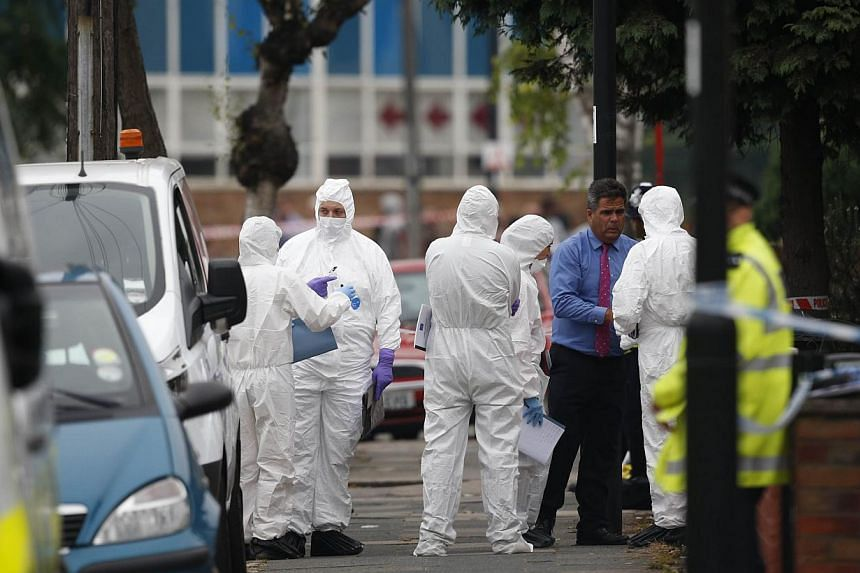 Police forensics personnel are pictured on a street in Edmonton, north London on Sept 4, 2014, after a woman was found dead following a suspected beheading in a residential garden. -- PHOTO: AFP