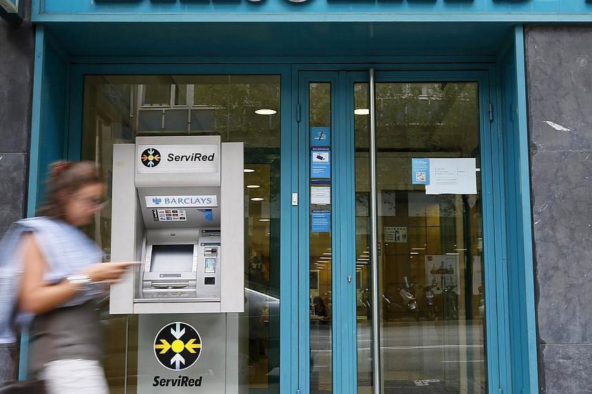 A woman walks past a Barclays bank office in Barcelona on Sept 1, 2014. -- PHOTO: REUTERS