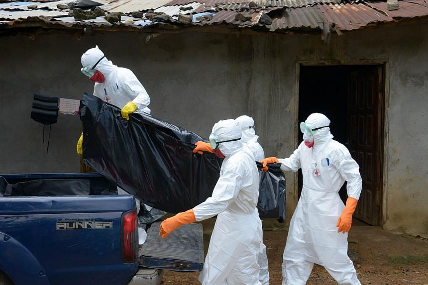 Medical workers of the Liberian Red Cross, wearing a protective suit, carry the body of a victim of the Ebola virus in a bag on Sept 4, 2014, in the small city of Banjol. -- PHOTO: AFP