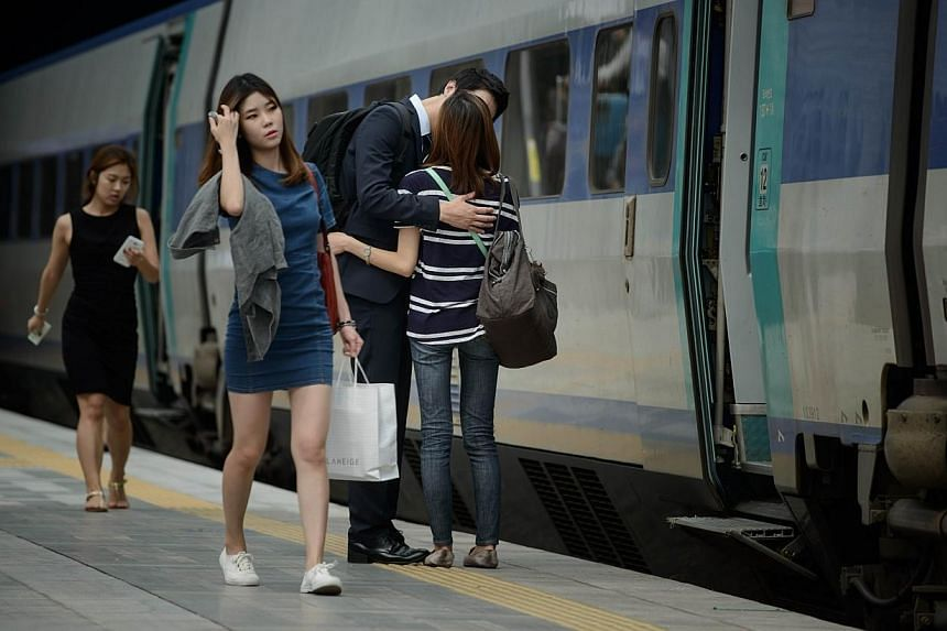 A couple kiss as they bid farewell at a railway station ahead of the annual Chuseok holiday, in Seoul on Sept 5, 2014.Fake casts for pretending you have an injured arm to evade having to help prepare holiday meals have become brisk sellers in S