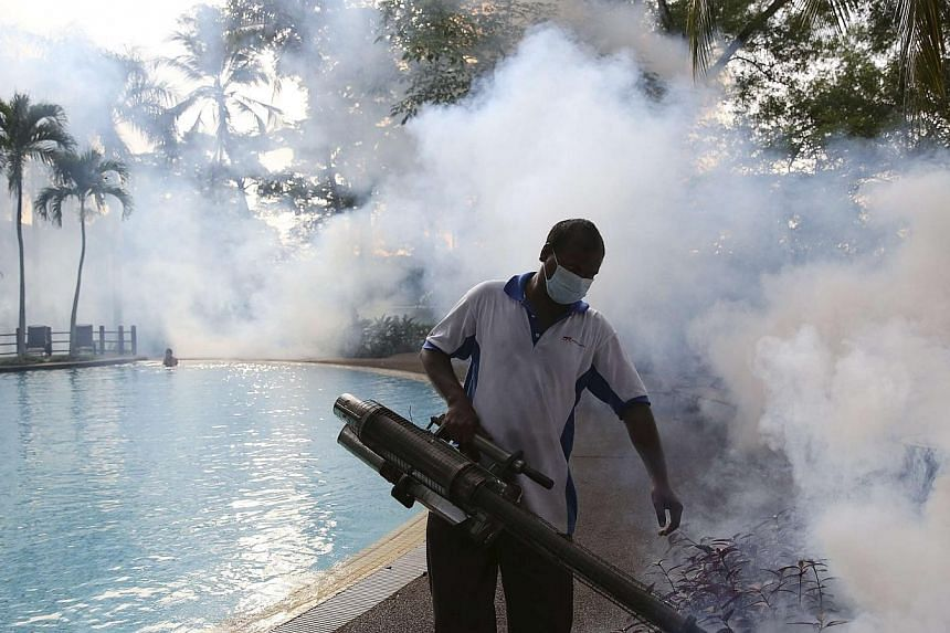 A pest control worker sprays insecticide to help control the spread of dengue fever carried by mosquitoes in Kuala Lumpur on Aug 27, 2014. Malaysia is reeling from a deadly outbreak of dengue, with nearly four times more deaths so far this year