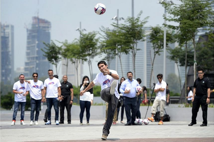 Deco attempts to kick a ball into the dome of the National Stadium at the Sports Hub. -- ST PHOTO: DESMOND LIM