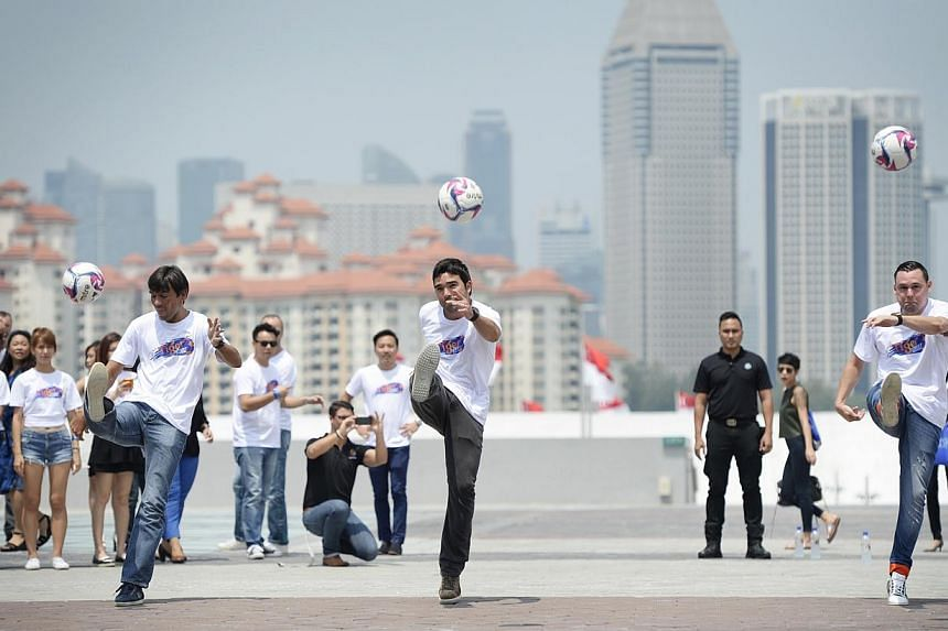 (From left) Paulo Ferreira, Deco and Maniche attempt to kick a ball each into the dome of the National Stadium at the Sports Hub. -- ST PHOTO: DESMOND LIM