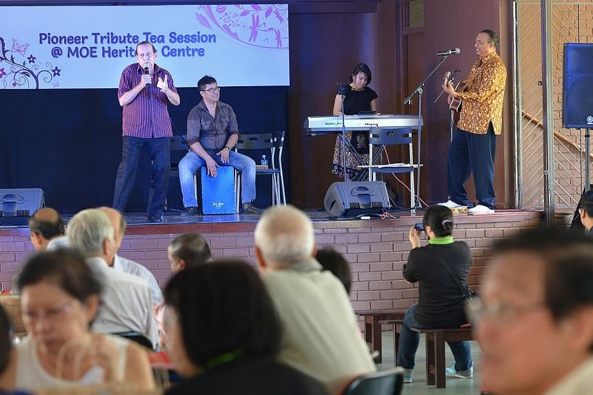 Former teacher Harold Mathieu (on stage), 75, belts out a song at the first in a series of tea sessions for pioneers at the MOE Heritage Centre. -- ST PHOTO: NG SOR LUAN