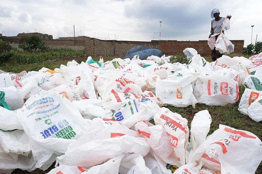 A woman sorts out plastic bags after washing them for re-use at the shores of a river on June 24, 2014, in Nairobi.California Governor Jerry Brown said late on Thursday that he would approve a ban on single-use plastic bags, in what would make