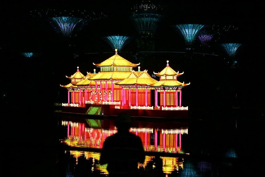 A man's silhouette is cast against the reflections of the lantern display and the supertrees in the background. -- ST PHOTO: ONG WEE JIN