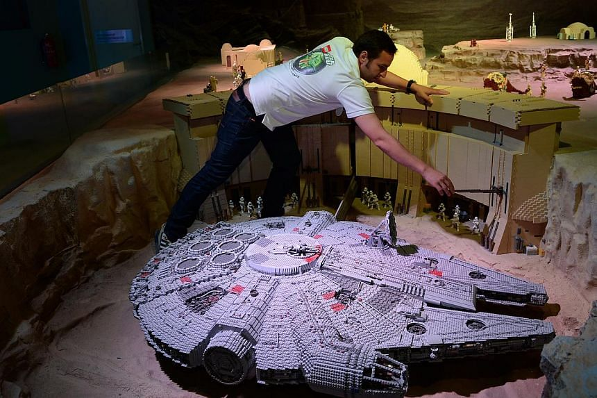Lego master builder and Legoland Malaysia model shop manager Stefan Bentivoglio adjusting some pieces in the Millennium Falcon display area, on Sept 3, 2014. -- ST PHOTO: JOYCE FANG