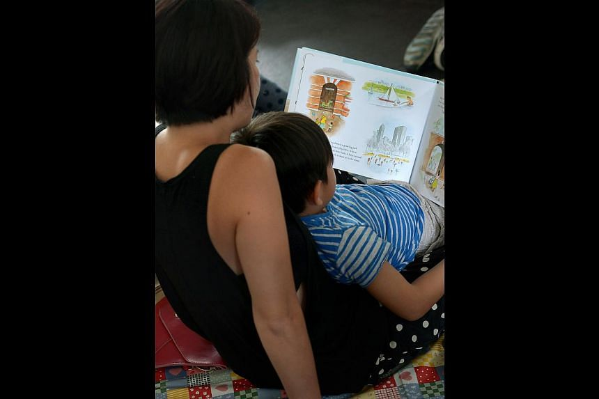 A mother reading And Tango Makes Three, a book NLB had pulled, to her child at a reading event.