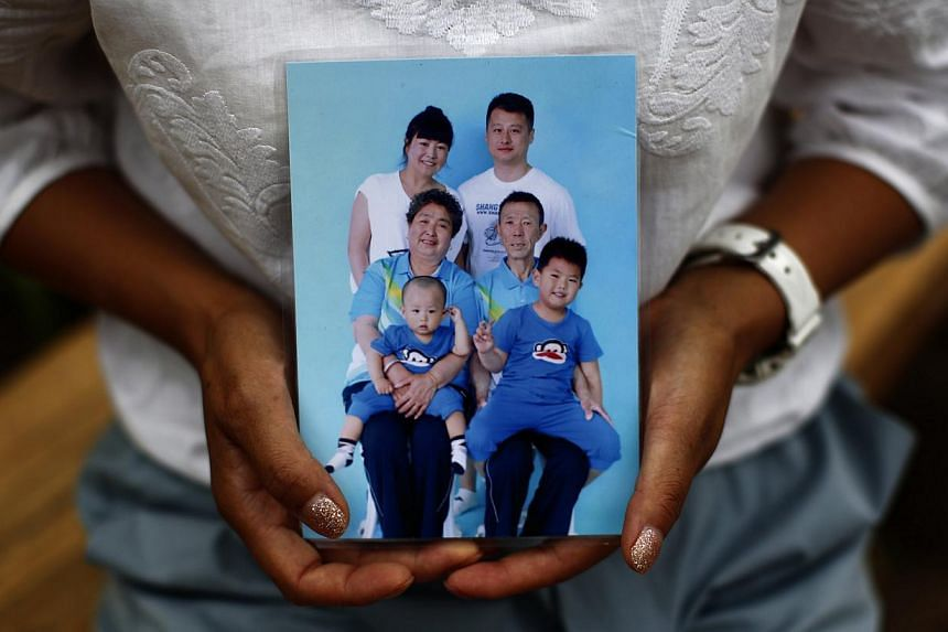 Cheng Liping, whose husband Ju was onboard Malaysia Airlines Flight MH370, shows a family photo featuring her missing husband (top, right) at a park in Beijing on July 24, 2014. -- PHOTO: REUTERS